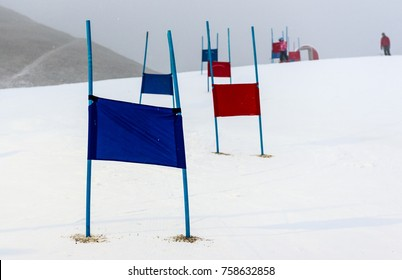 Children skiing slalom racing track with blue and red gates. Small ski race gates on a pole with children skiing in the background.