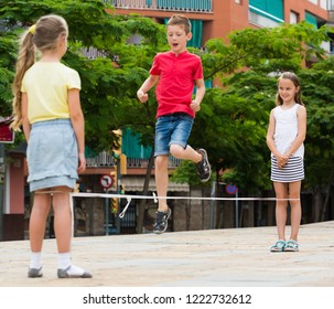 children skipping together with chinese jumping rope urban playground