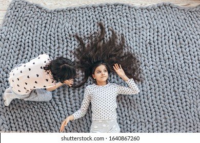 Children in sleepwear lying down and playing with each other on chunky giant woolen blanket, top view