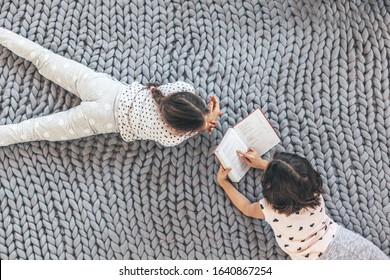 Children in sleepwear lying down and relaxing with a book on chunky giant woolen blanket, top view