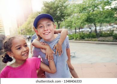 Children smiling walking in the center of a city