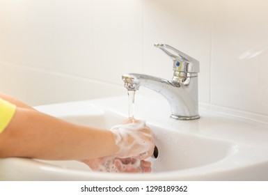 Children with soapy hands washed in bathroom sink.