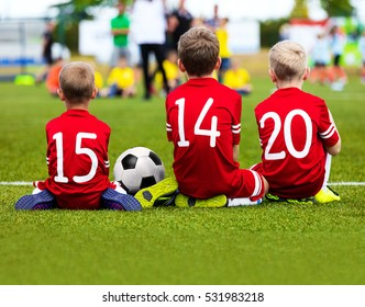Children Soccer Team Playing Match. Football Game for Kids. Young Soccer Players Sitting on Pitch. Little Kids in Red Soccer Jersey Sportswear