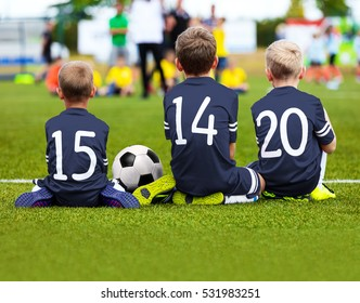 Children Soccer Team Playing Match. Football Game for Kids. Young Soccer Players Sitting on Pitch. Little Kids in Blue Soccer Jersey Sportswear
