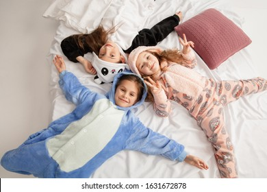 Children in soft warm pajamas colored bright playing at home. Little girls having fun, party, laughting, playing together, look stylish and happy. Concept of childhood, leisure activity, happiness.