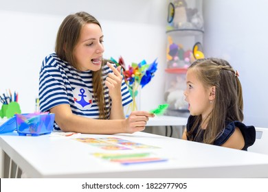 Children speech therapy concept. Preschooler practicing correct pronunciation with a female speech therapist.