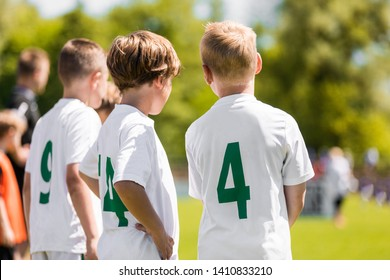 Children Sports Team Members. Junior Soccer Players on Substitution Bench. Kids in White Jersey Shirts with Green Numbers on its Back