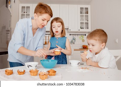 Children sprinkle cupcakes with colored caramel for Easter and eat.