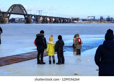 Children stand on the ice of a frozen river and watch the winter swimming. Winter sport and hardening. Dnipro city, Dnepropetrovsk, Ukraine