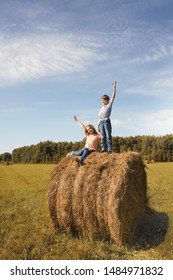 Children standing on hay bale in a field. Harvest, Freedom, happy childhood, healthy lifestyle concept.