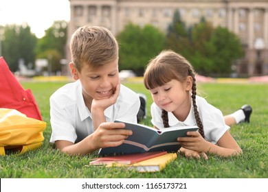 Children with stationery doing school assignment on grass outdoors