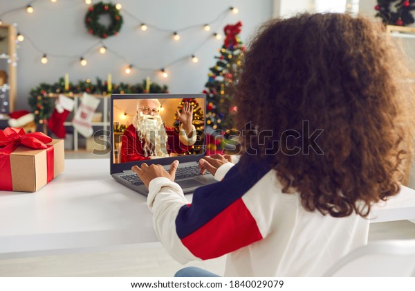 Children stay at home due to the lockdown and have virtual Christmas celebration. Over shoulder view of African-American girl having video call with Santa Claus sitting at desk in decorated room