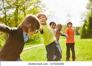 Children in summer camp hold hands as friends on a meadow in the park