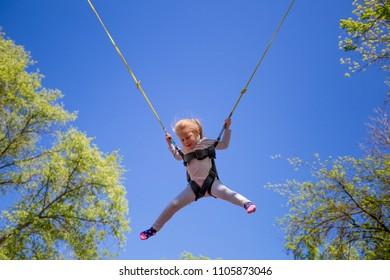 Children summer entertainment. Little girl jumping on children trampoline on blue sky backdrop. Child happiness theme.