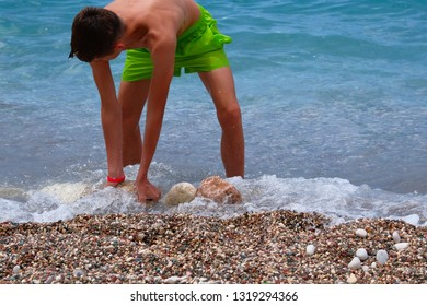 Children summer vacation at sea. Sunburnt school boy builds a tower of stones on sea coast. Active sunny summer day.