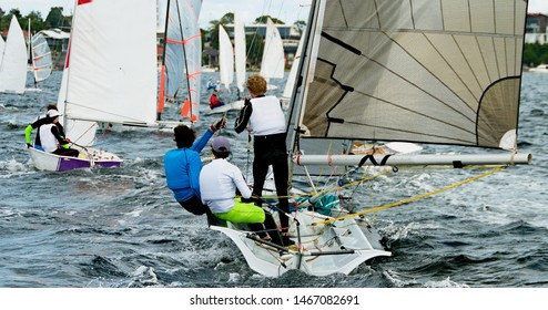 Children supervised colourful sailing activities in all types of small boats and dinghies in fun and competition. Teamwork by junior sailors racing on salt water Lake Macquarie.