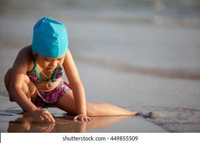 Children swim beach at sunset