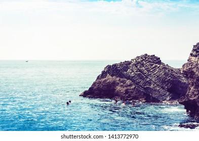 Children swim near Acitrezza rocks of the Cyclops, sea stacks in Catania, Sicily, Italy