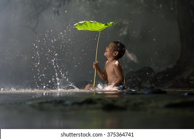 Children swim in the streams of light shine a little at Nong Khai in Thailand.People are enjoying a holiday in the woods. lifestyle , adventure , nature background ,beautiful landscape , waterfall