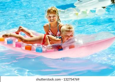 Children swimming on inflatable beach mattress.
