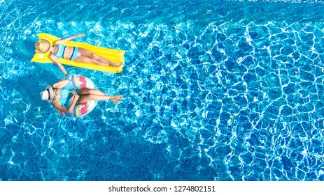 Children in swimming pool aerial drone view fom above, happy kids swim on inflatable ring donut and mattress, active girls have fun in water on family vacation on holiday resort