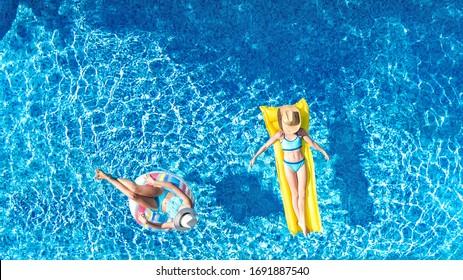 Kinder im Schwimmbad, Draufsicht von oben, glückliche Kinder schwimmen auf aufblasbaren Ring Donut und Matratze, aktive Mädchen haben Spaß im Wasser im Familienurlaub im Ferienort