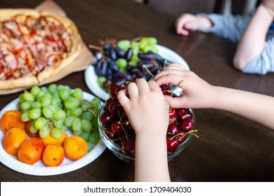 Children at the table are treated to fruit and berries from plates