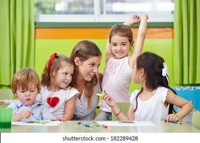 Children talking to nursery teacher in kindergarten while painting pictures