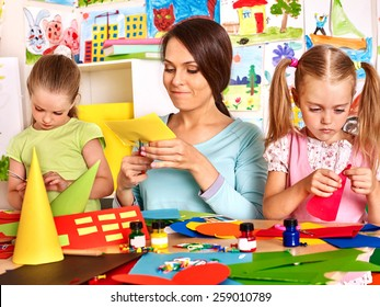 Children  with teacher cutting out scissors paper in preschool.