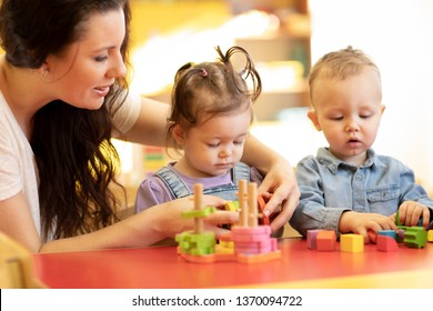 Children with teacher play with shapes and colorful wooden puzzle in a montessori classroom