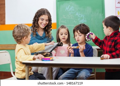 Children and teacher playing with musical instruments in preschool