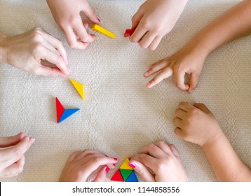Children and Teacher playing Tangram together.