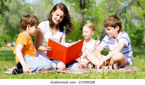 children and teacher reading book together in the summer park