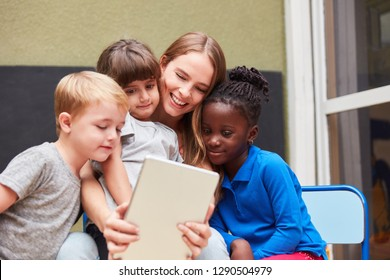 Children and teacher using a tablet PC use an app for learning and playing