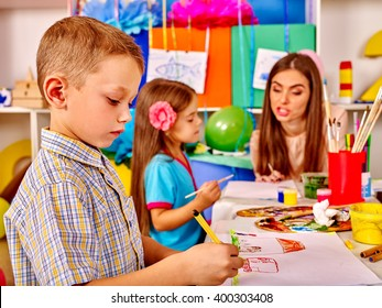 Children with teacher woman painting on paper at table  in  kindergarten . Clever boy on foreground.