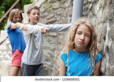 Children tease the girl. Boy and girl teasing kid