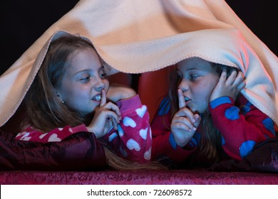 Children and technology concept. Kids wearing red jammies in bed on black background. Pyjamas party for children. Girls shushing with their fingers on lips. Girl friends play under blanket
