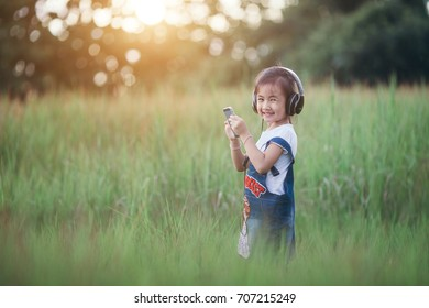 Children, technology and leisure concept - girl with headphones lying on natual and listening to music .