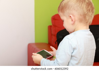 Children and technology, spending free time online concept. Little boy using smartphone playing games