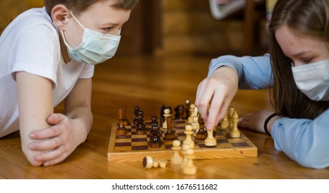 Children teenagers boy and girl, brother and sister play chess in medical masks on the face, lie on the floor. Quarantine, virus, infection, coronavirus, isolation.