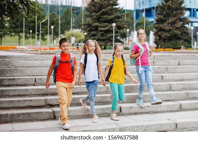 Children teenagers in colorful clothes with backpacks are walking up the stairs to school.