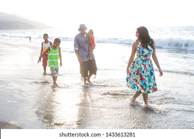 children and their dad with kite at the beach walking