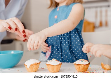 Children with their hands sprinkle cupcakes with colored caramel for Easter. Concept happy family.