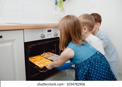 Children with their mother in kitchen are waiting for cookie to cook in oven.