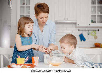 Children with their mother try cooked breakfast porridge. Concept healthy food.