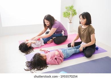 Kinder und ihre Mütter, die Yoga im Innenbereich machen