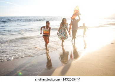 Children and their parents  with kite at the beach runing