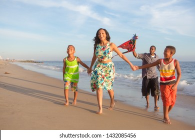 children and their parents  with kite at the beach walking