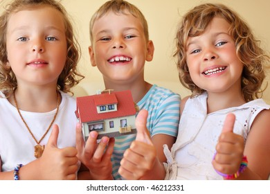 children three together keeping in hands model of house in cozy room, shows ?? gesture