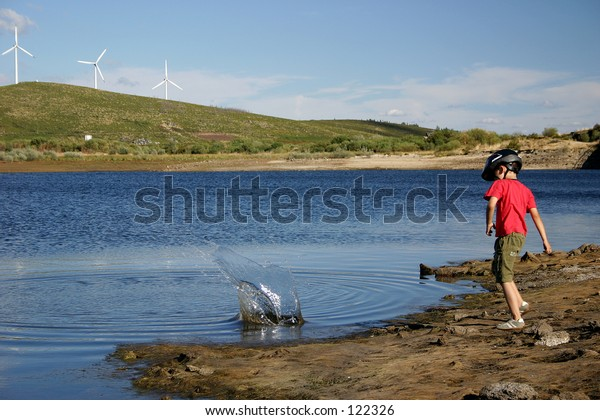 Children throwing stones to the lake